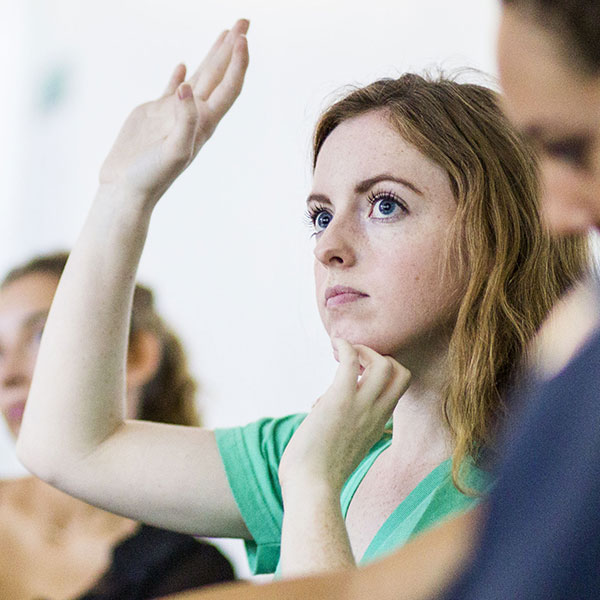 Woman raising her hand in class.